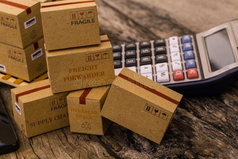 Scatole di cartone che imballano i prodotti ed il calcolatore sui tum di legno immagini stock