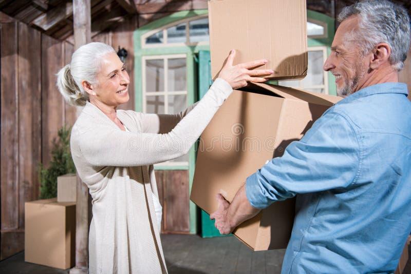 Scatole di cartone senior della tenuta delle coppie mentre entrando nella nuova casa immagini stock