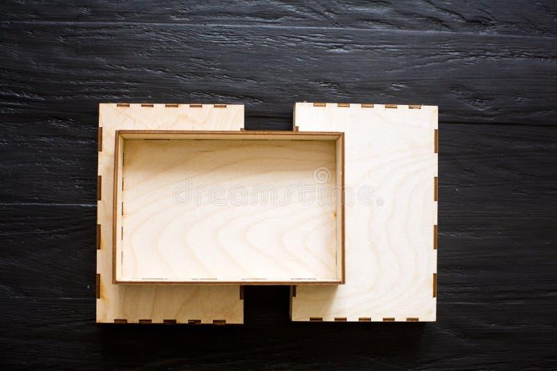 Scatole di legno di compensato su un fondo di legno nero immagini stock libere da diritti