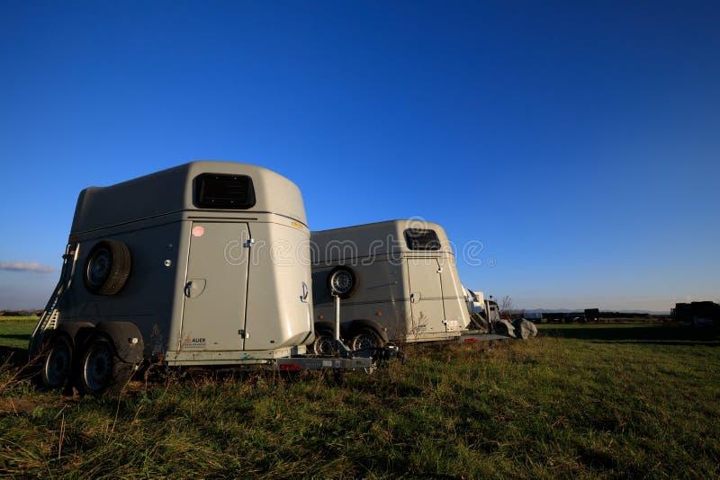 Scatole di trasporto del cavallo che stanno su un campo fotografia stock