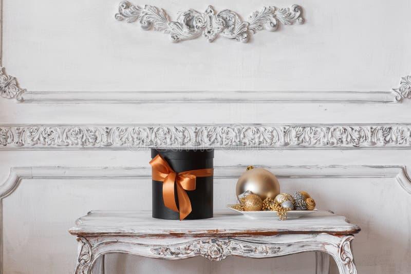 Scatole nere avvolte del regalo con i nastri come i regali di Natale su una parete bianca di lusso della tavola progettano lo stu immagini stock