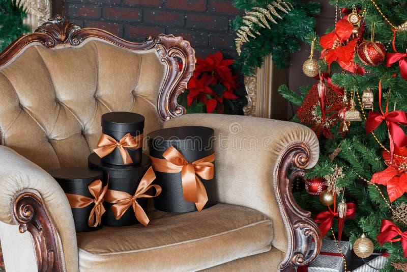 Scatole nere avvolte del regalo con i nastri come regali di Natale su una sedia immagini stock libere da diritti