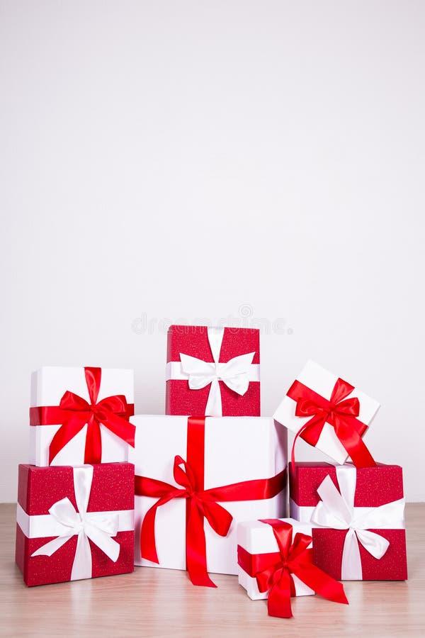 Scatole rosse e bianche del fondo di Natale - di regalo sul pavimento di legno immagini stock libere da diritti