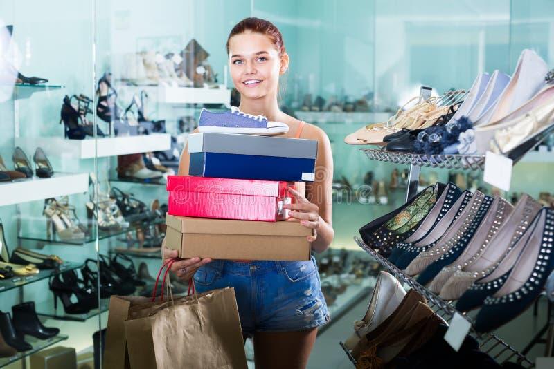 Scatole teenager allegre della tenuta della ragazza nel boutique delle scarpe fotografia stock libera da diritti