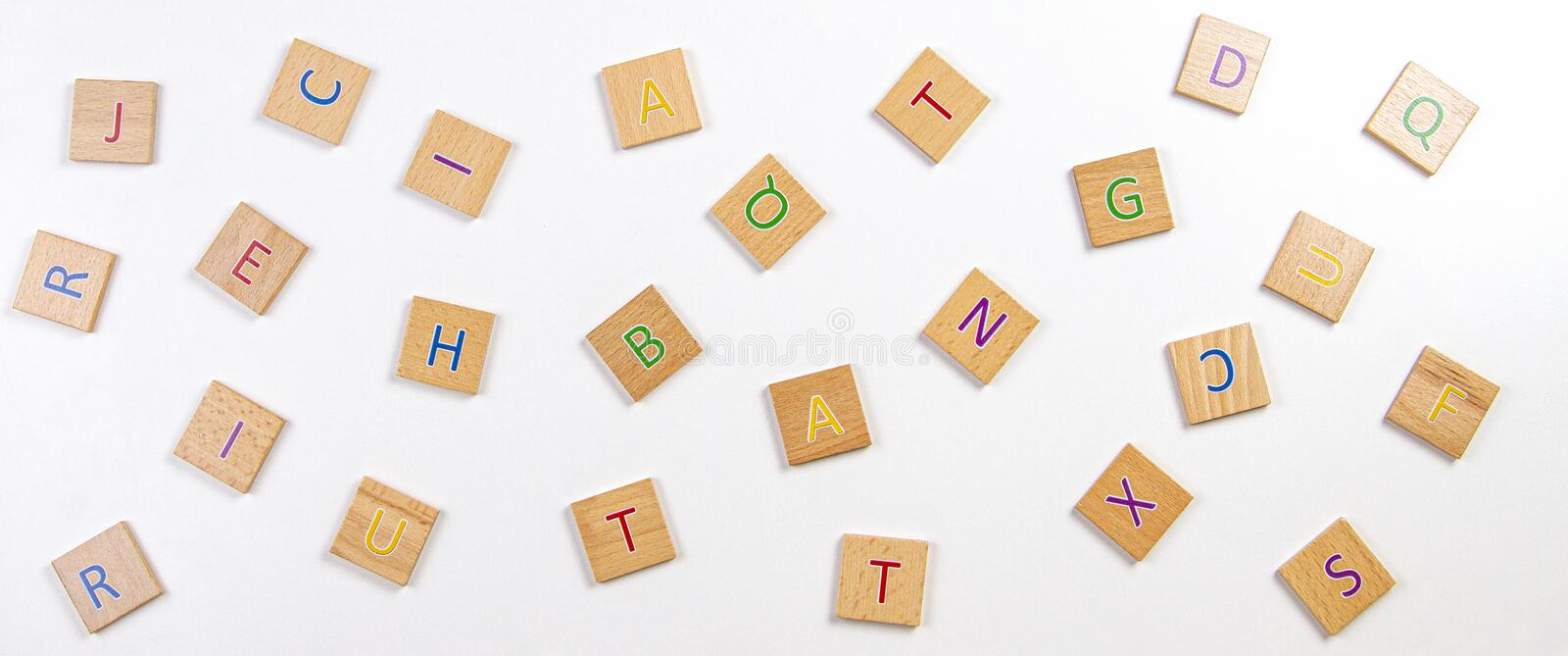 Scattered alphabet letters wooden blocks tiles on white table background. Top view stock photo