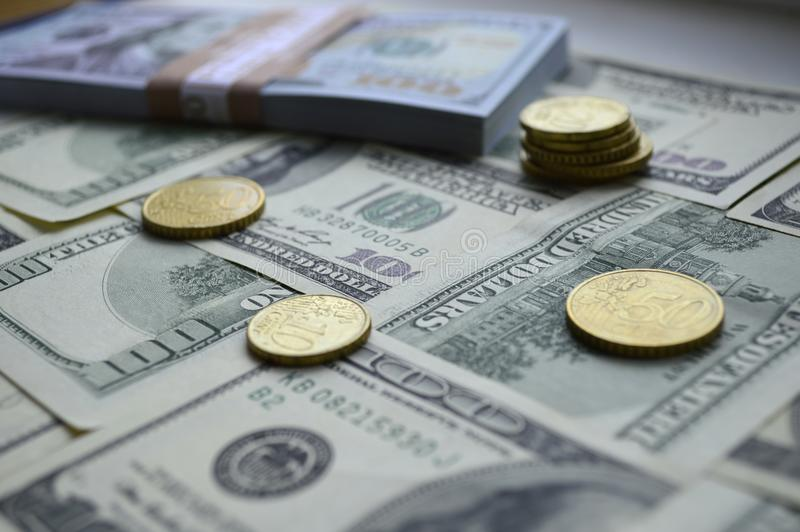 Scattered banknotes of 100 US dollars and euro coins royalty free stock photos