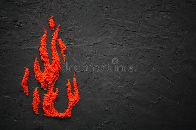 Scattered on the black surface of the red paprika in the form of flame petals. Red spices. Texture. Isolated stock photography