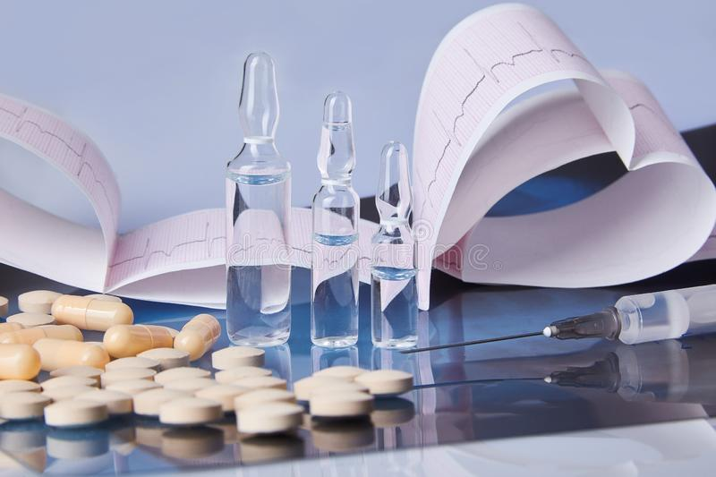 Scattered capsules, tablets, ampules and syringe on the table stock photo