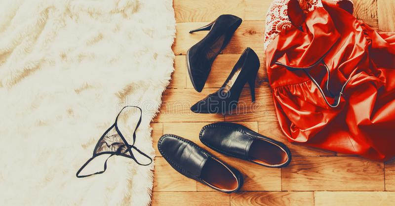 Scattered clothes and lovers shoes. Night of love. Selective focus stock photo