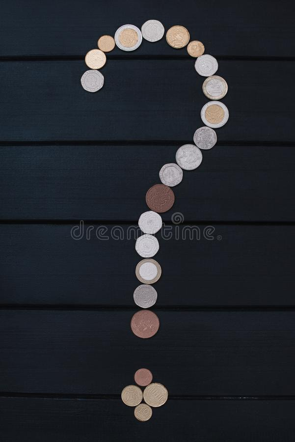 Scattered coins of different countries in the form of a question mark point on wooden table. finance concept stock image