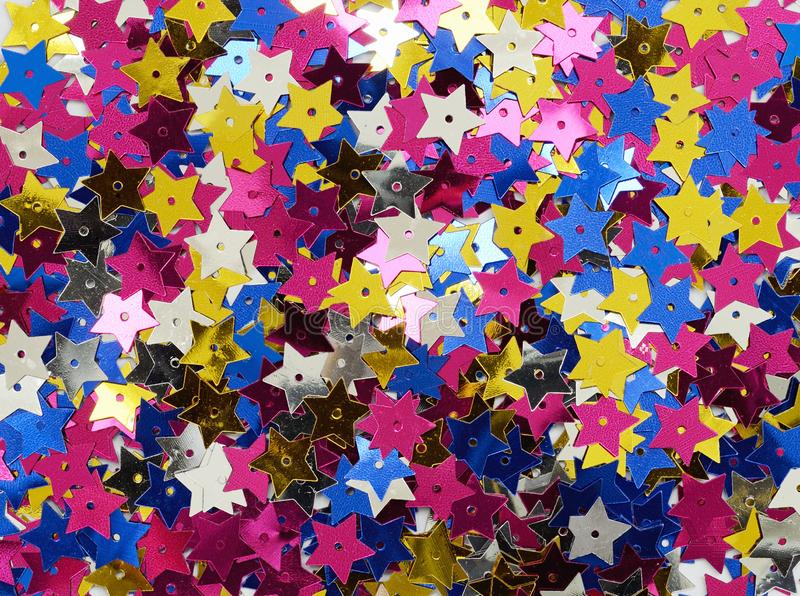 Scattered colorful star shape sequins. For holiday background stock image