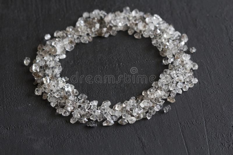Scattered diamonds on a black background. Raw diamonds and mining, a scattering of natural diamond stones. Graphite quartz. Natural stones and minerals. Frame royalty free stock images