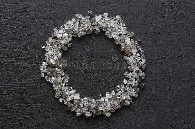 Scattered diamonds on a black background. Raw diamonds and mining, a scattering of natural diamond stones. Graphite quartz. Natural stones and minerals. Frame stock image