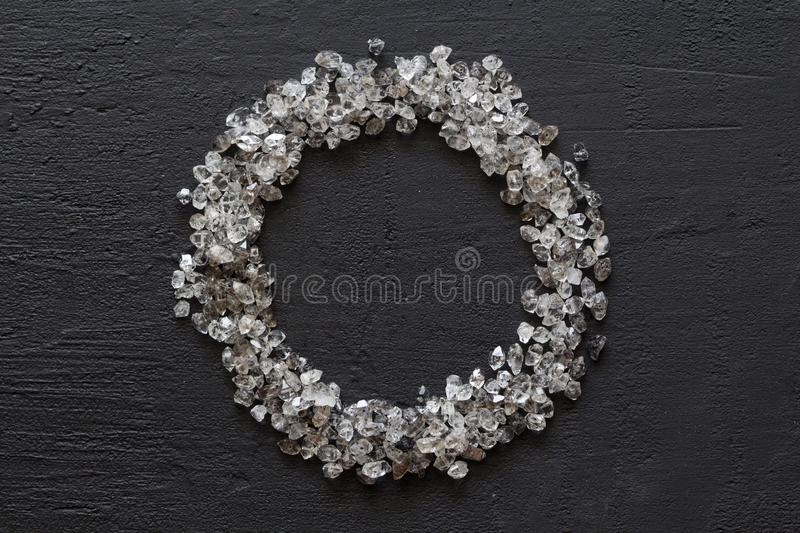 Scattered diamonds on a black background. Raw diamonds and mining, a scattering of natural diamond stones. Graphite quartz. Natural stones and minerals. Frame royalty free stock image