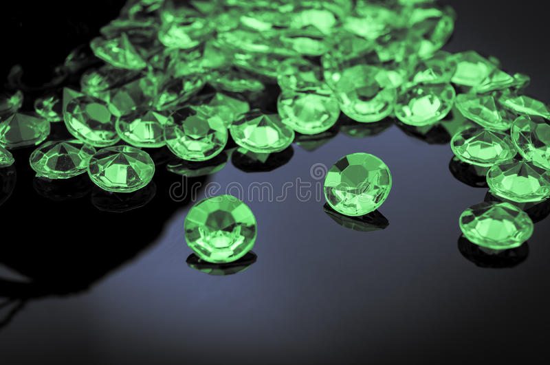 Scattered emeralds. Emeralds scattered on a shiny surface with prominent emerald in the middle stock image