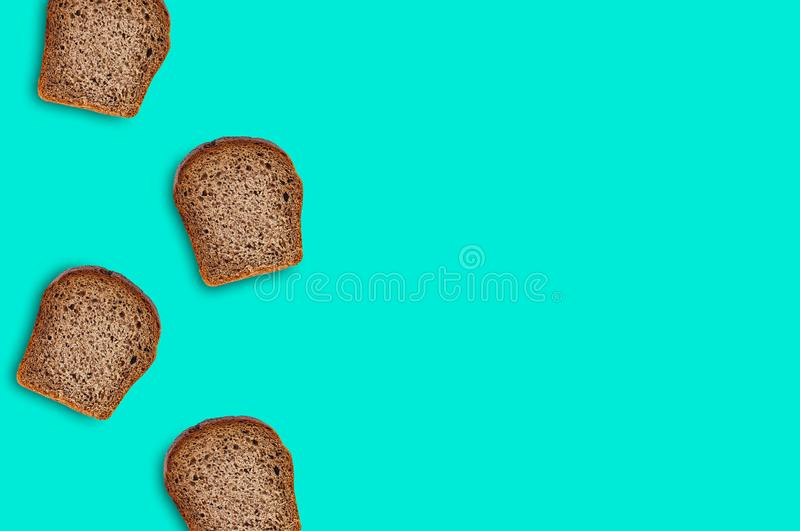 Scattered four rectangular pieces of fresh rye bread on green table on kitchen. Copy space for your text. Top view. Dieting concept stock photo