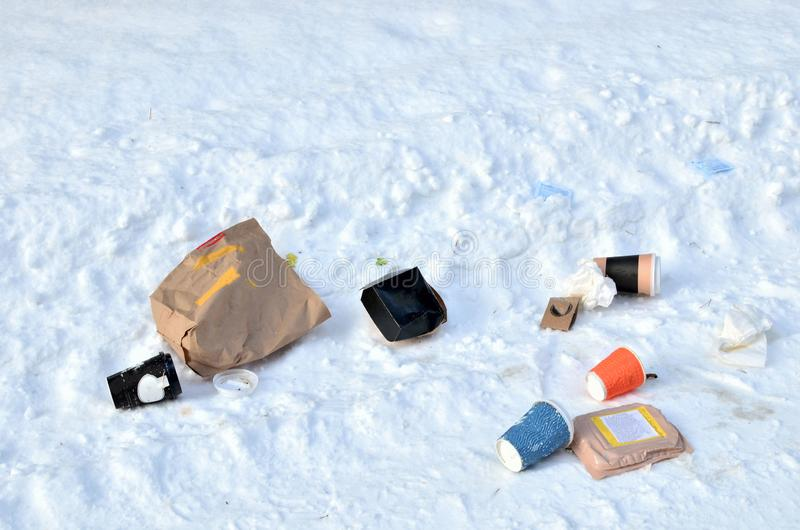 Scattered garbage in the city on the road in the snow. stock images