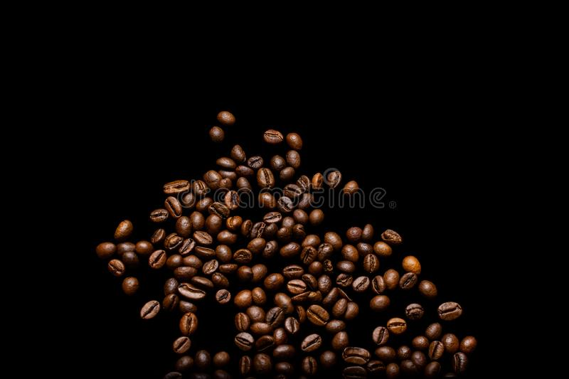Scattered grains of roasted, fragrant coffee on a black background, isolation, flat-lay, copy space royalty free stock images