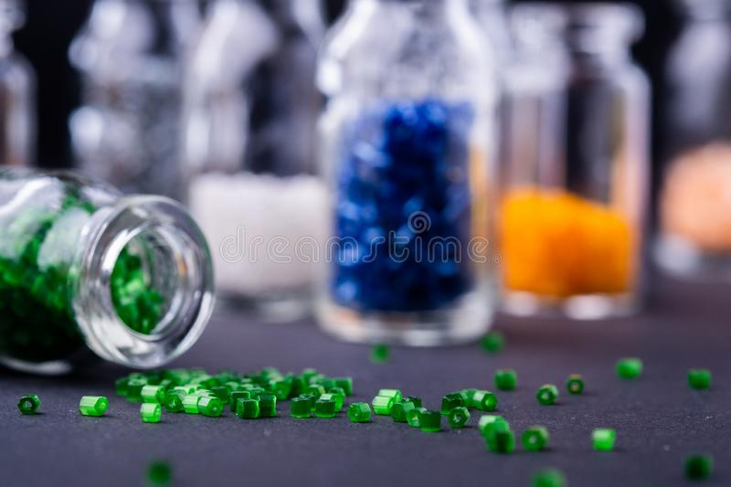 Scattered green beads from transparent bottle near varied colors beads dark background. Macro royalty free stock images