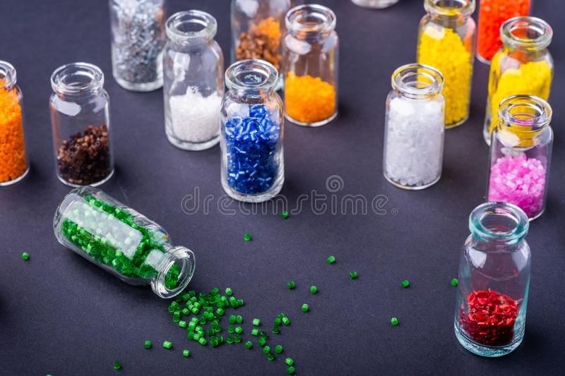 Scattered green beads from transparent bottle near varied colors beads dark background. Macro stock images