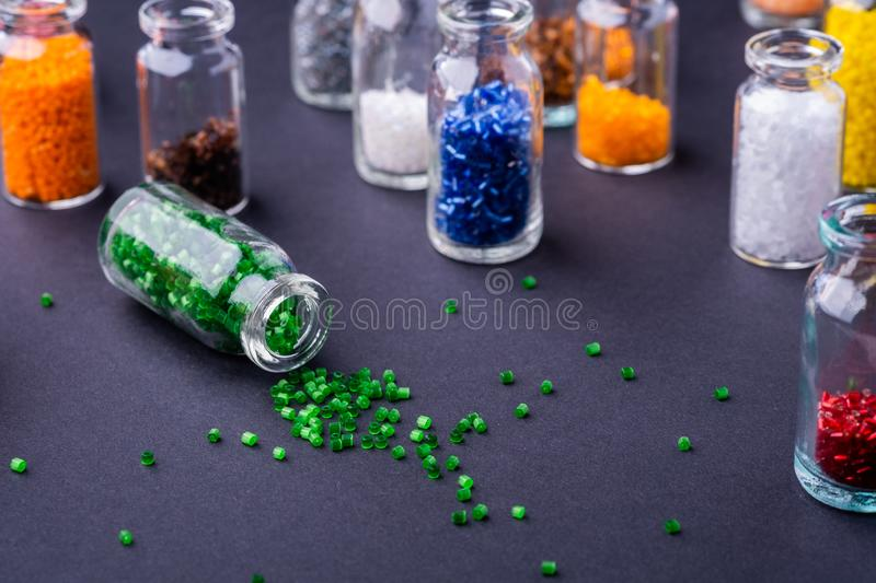 Scattered green beads from transparent bottle near varied colors beads dark background. Macro royalty free stock photography