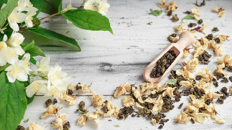 Scattered green tea leaves with jasmine flowers stock photo