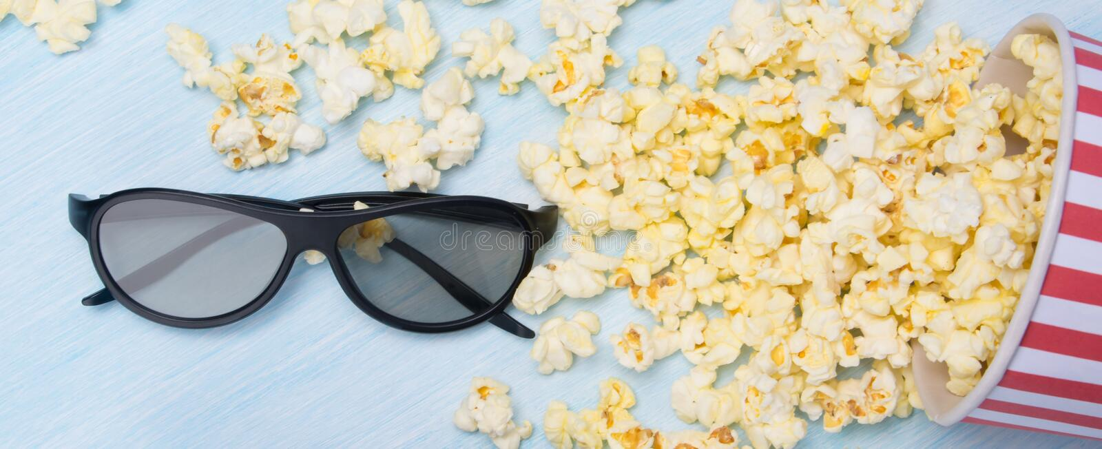 Scattered on a light gray background, popcorn in a bucket and 3 d glasses stock photography