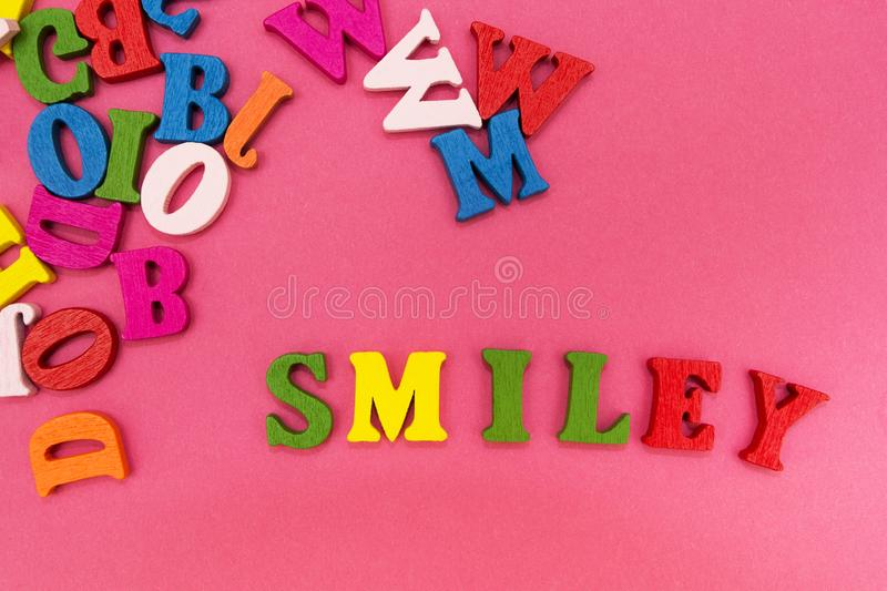 Scattered multicolored letters on a pink background, the word. `smiley royalty free stock photos