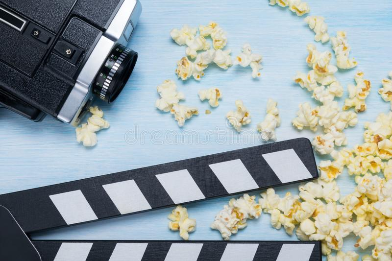 Scattered popcorn with film strip, concept on a blue background royalty free stock image