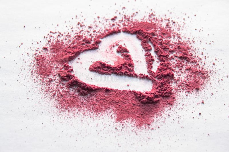 Scattered powder with heart pattern on white  background, top beauty make-up stock image