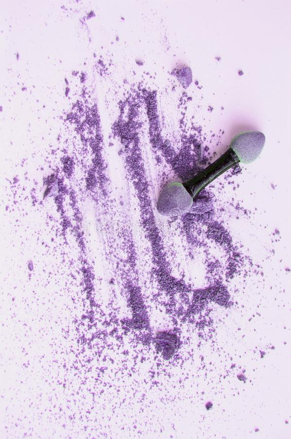 Scattered purple and lilac eyeshadow with applicator,  on white background, beauty and makeup concept, vertical shot. Blue gray crumbs powder cosmetology brush stock photos