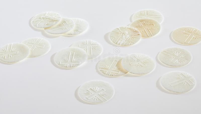 Scattered sacramental Hosties on white. Scattered sacramental Hosties on a white background symbolic of the body of the resurrected Christ used in Holy Communion royalty free stock images
