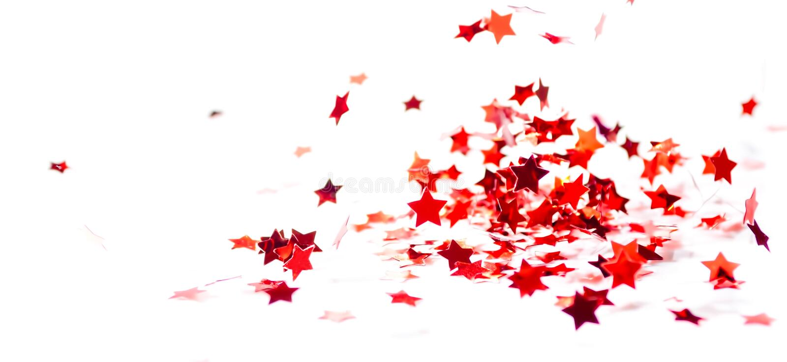 Scattered small red glossy confetti stars fly