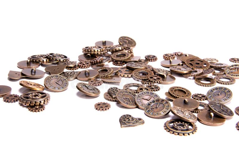 Scattered vintage steampunk copper metal buttons on a white background, shaped as gears, hearts, and clock pieces. Scattered vintage copper metal buttons on a stock photos