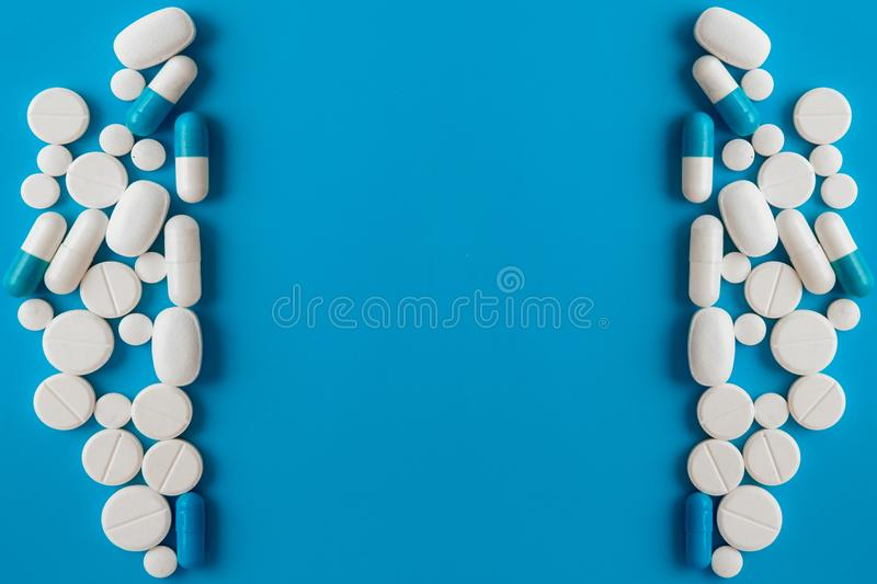 Scattered white pills on blue table. Mock up for special offers as advertising, web background or other ideas. Medical, pharmacy. And healthcare concept. Copy stock photos