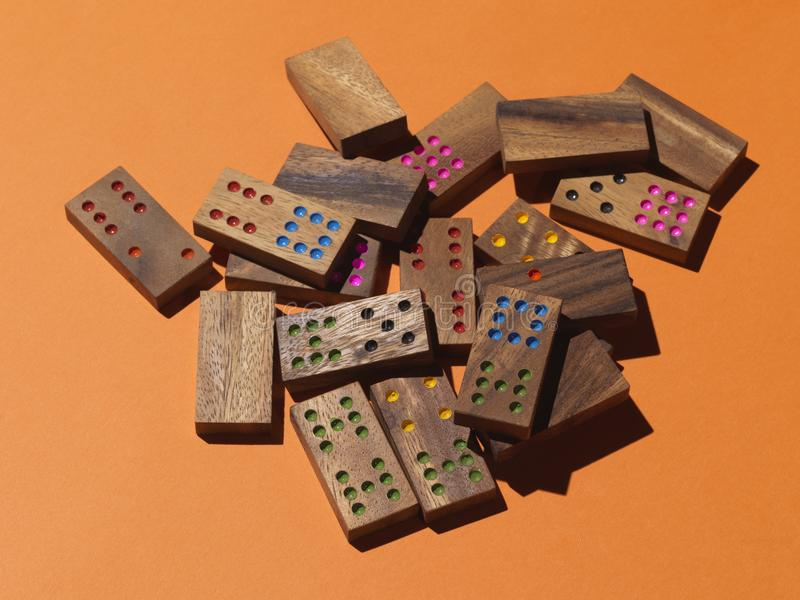 Scattered domino pieces on orange background stock photos