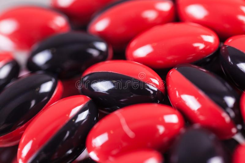 A scattering of red-black brown pills on the mirror background stock photography