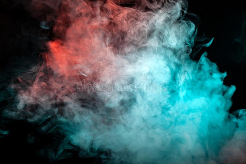 A scattering white cloud of dense smoke, illuminated by different colors and exhaled from a cigarette, rolls up in waves, rising royalty free stock photos
