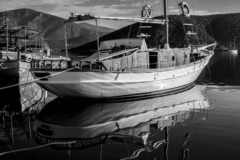 Scatto in scala di grigi di una nave a vela nell'acqua con montagne rocciose alte sullo sfondo fotografia stock libera da diritti