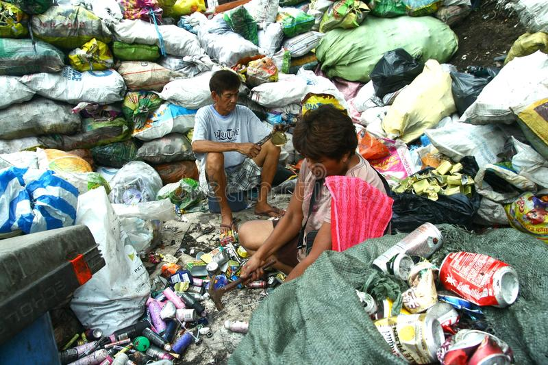 Scavengers preparing segregated recyclable waste products to be sold to recycling facilities. Scavengers at a dump site called Smokey Mountain in Manila royalty free stock image