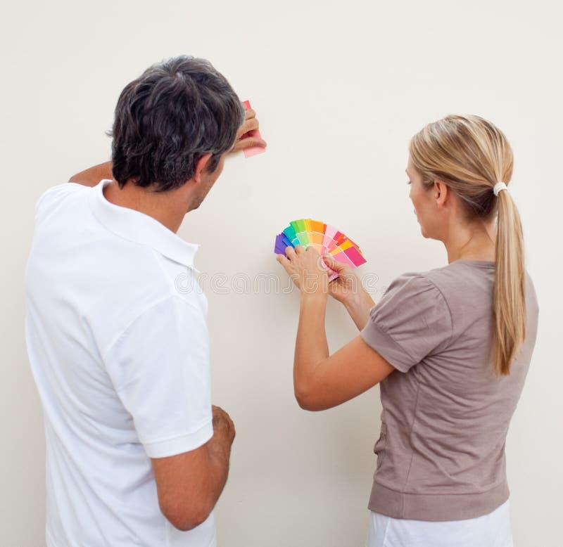 scegliendo il colore le coppie verniciano la stanza a fotografia stock