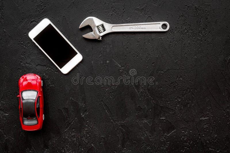 Scelga il servizio dell'automobile Strappi vicino ai giocattoli ed al telefono cellulare dell'automobile sul copyspace nero di vi fotografia stock