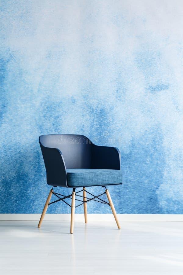 Scelga la sedia moderna dei blu navy che sta contro il blu e il wh vuoti immagini stock