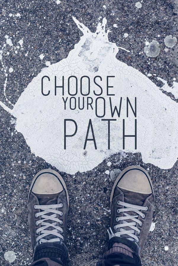Scelga la vostra propria citazione motivazionale del percorso sul backgro urbano dell'asfalto fotografia stock libera da diritti