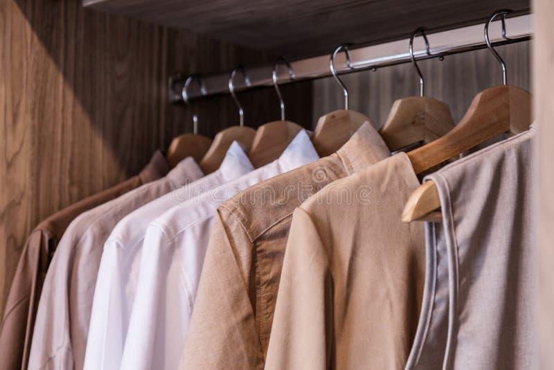 Scelta dei vestiti di modo dei colori differenti sui ganci di legno fotografia stock