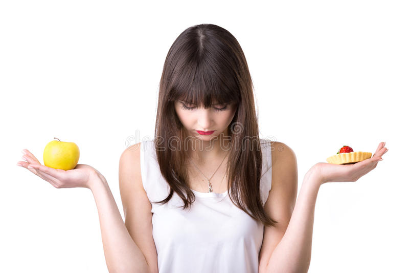 Scelta dell'alimento per la donna stante a dieta fotografia stock