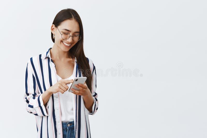 Scelta della carta da parati nuova sullo smartphone Ritratto della donna attraente ed alla moda felice in vetri e blusa a strisce fotografie stock