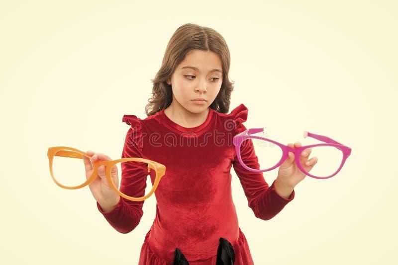 Scelta dura Accessorio degli occhiali della tenuta del bambino Fondo bianco isolato bambino La ragazza sceglie i grandi occhiali  fotografia stock libera da diritti