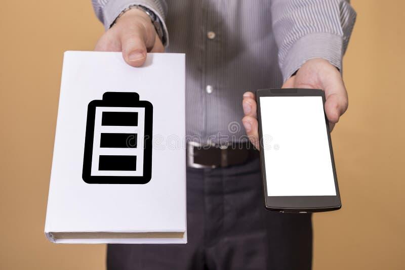 Scelta fra il libro e la durata di vita della batteria del cellulare immagini stock