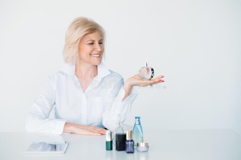 Scelta invecchiata alla moda sorridente del profumo di stile di vita di signora immagini stock